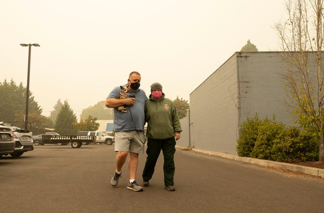 Upper Mckenzie Fire Chief Christiana Rainbow Plews (right) and her husband Eric Plews walk in the parking lot of their hotel in Eugene. Chief Rainbow ordered a Level 3 evacuation of her Blue River community, which included her family, from the advancing flames of the Holiday Farm Fire.