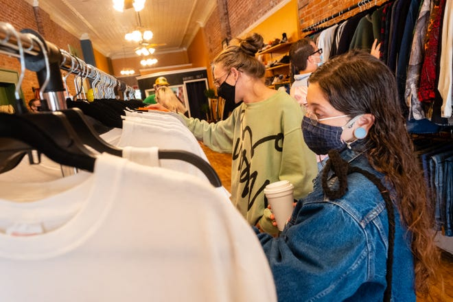 Ian Burkett, left, and Samantha Shovan, both of Port Huron, browse through vintage clothing at Main Street Ensemble during the store's grand opening Monday, Sept. 14, 2020, in downtown Port Huron.