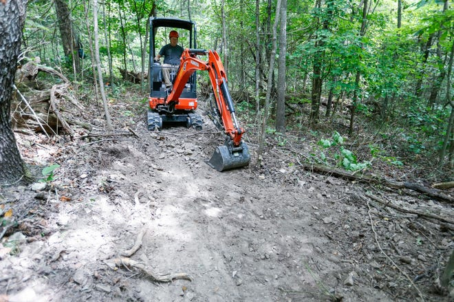 Progressive Trail Design foreman David Renko runs a mini track hoe to work on the construction of a new 6.65-mile long mountain biking and walking trail around Fellows Lake on Monday, Sept. 14, 2020.