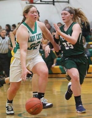 Milan's Cady Pauley, left, competes Tuesday evening during high school basketball action against Polo at Milan High School.