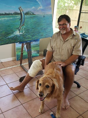 Mark Johnson, 61, a marine artist from Port St. Lucie, is glad he can smile alongside his faithful golden retriever, Rex, after being grabbed by an alligator behind his home on Sept. 13, 2020.