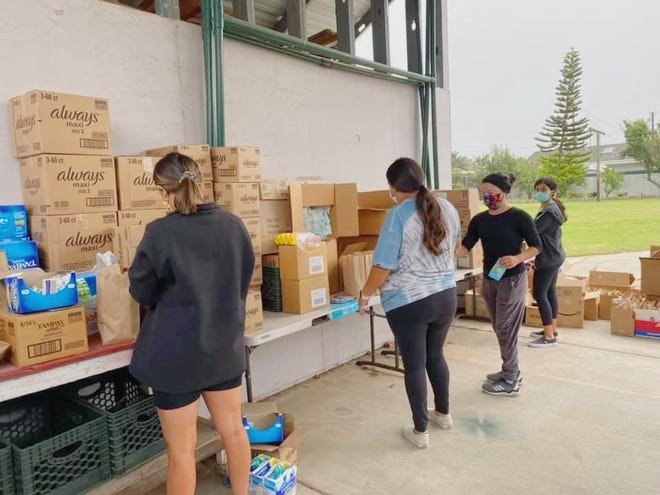 Volunteers with Oxnard Student Success put together supplies, including sanitary napkins as pictured, for families to take during a giveaway Sunday, Sept. 13, 2020.