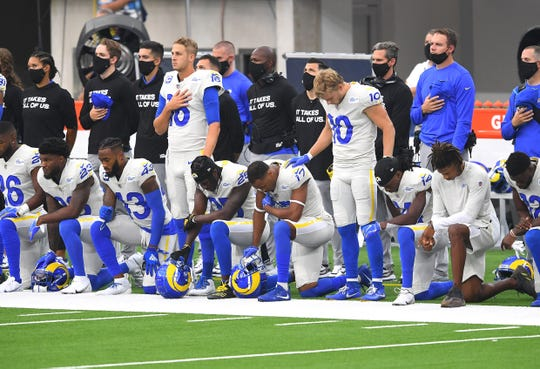 Los Angeles Rams players shown on the sidelines during the national anthem before the game against the Dallas Cowboys at SoFi Stadium.