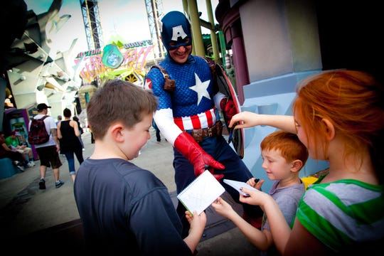 Pre-COVID, children at Universal Orlando's Islands of Adventure got Captain America's autograph. Now such encounters are socially distanced or off-limits.
