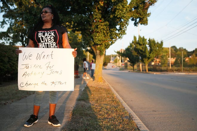Crystal Hanes, cousin of Antony Jones, holds a sign at a candlelight vigil for Jones outside the Summit County Jail on Sept. 22, 2017, in Akron.