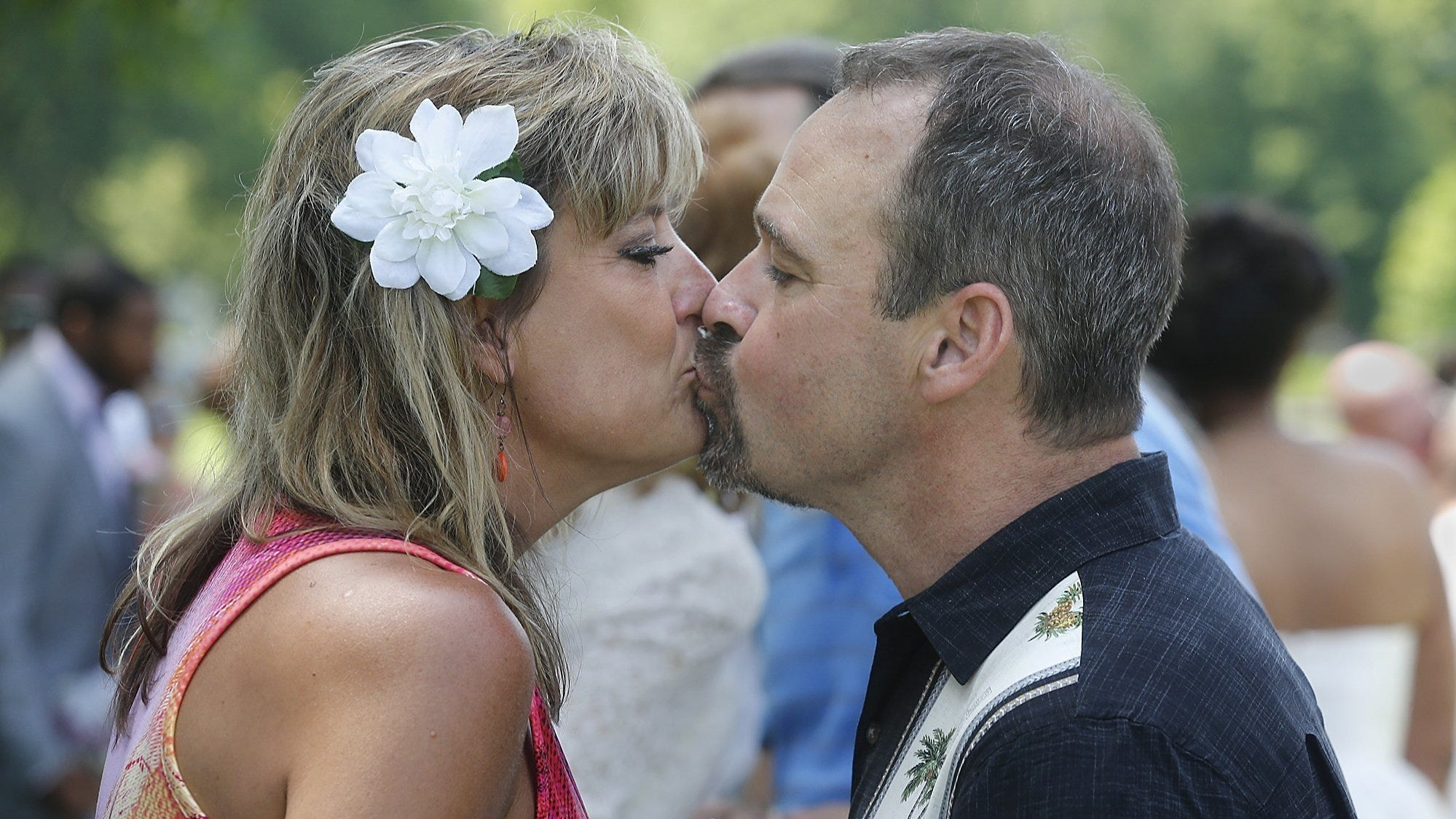 Shannon and Tom Hasenstab of Cuyahoga Falls kiss after Summit County Probate Court Judge Elinore Marsh Stormer renewed their wedding vows with 34 other couples in June 2019. Many couples postponed weddings or drastically cut the guest lists in 2020 because of the pandemic. [Phil Masturzo/Beacon Journal/Ohio.com]
