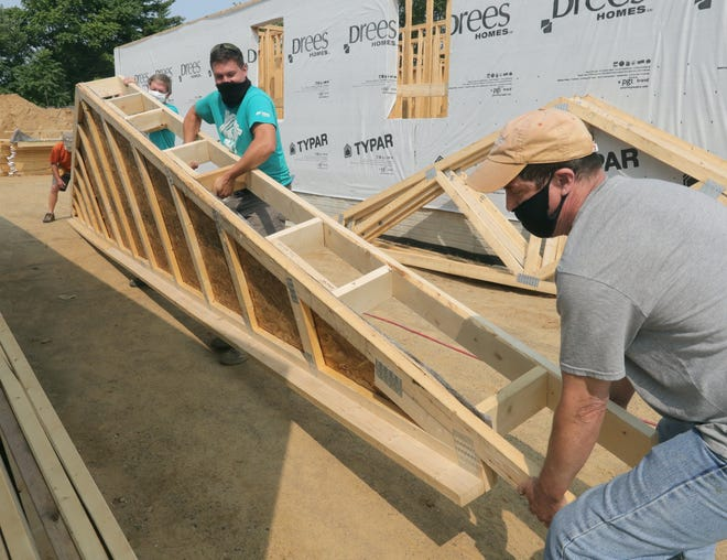 Site supervisor Will Yoho, center, moves a roofing truss Tuesday with help from Habitat for Humanity volunteer Mark Ailstock, right, and others during work on the East Avenue project in Akron. [Phil Masturzo/Beacon Journal]