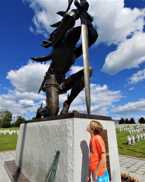 Carl LaVO's grandson Dashiell peers up at the statue of a Hussar soldier on the grounds of Our Lady of Czestochowa in New Britain Township.