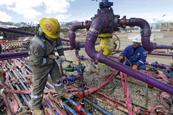 Workers tend to a well head during a hydraulic fracturing operation at an Encana Oil and Gas well in western Colorado. [The Associated Press file]