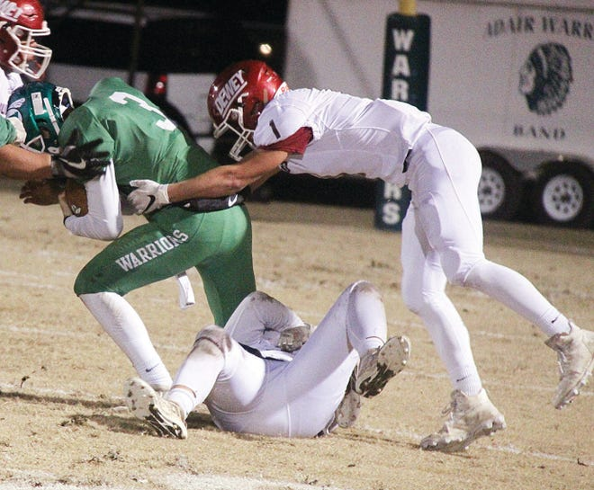 Dewey High's Jack Davis, right, helps bring down an Adair High ballcarrier during Class 2A football playoff action last season.