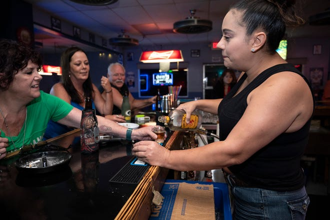 A bartender serves shots to customers at Crossroads 44 Music and Sports Bar in Eustis on their first day back in business. [Cindy Peterson/Correspondent]