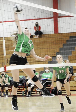 Barnesville senior Rylee Stephens (33) gets up high to spike the ball over the net with team mate Halle Markovich (33) ready to help out during Monday's volleyball match with host Caldwell.