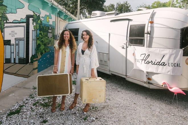 Co-founders of The Florida Local market Alonda McCarty, left, and Chelsea Preston, stand beside their brick and mortar location on Julia Street in New Smyrna Beach. They will run the shop out of their Avion bus, pictured, and travel around Florida.