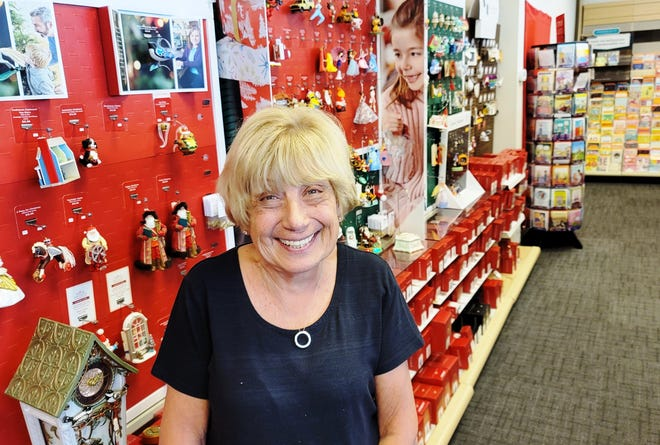Sandy Aldridge stands next to the Aimee's Hallmark Christmas display area. The Palm Coast store has been open since 1986.