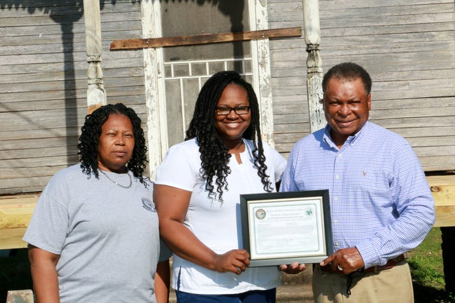 Last week, Donaldsonville Mayor Leroy Sullivan marked the beginning of a reconstruction project in the city's historic district by awarding a Certificate of Appropriateness. Shown, from left, are Doris Hall, Tenetian LaFarrah Hall, and Mayor Sullivan.
