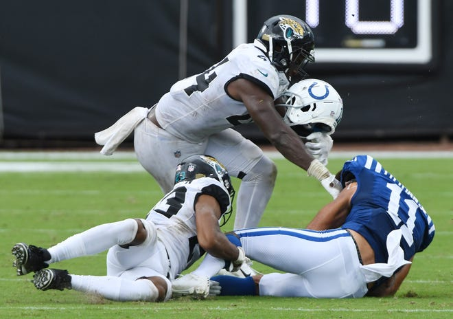 Colts wide receiver Michael Pittman (11) loses his helmet on a tackle by Jaguars cornerback C.J. Henderson (23) with an assist from linebacker Myles Jack (44).