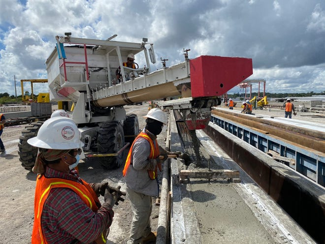 Workers with Gate Precast work on casting concrete for a bridge project. The company will fabricate the new 24- by 24-foot pilings for the Jacksonville Beach pier, and UNF's Dr. Adel El Safty plans to research the old failed pilings.
