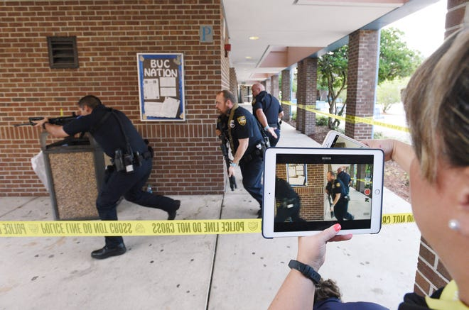 A former public information officer captures video as Jacksonville sheriff's officers and Duval County School Police respond during an active shooter training session at First Coast High School in 2018.