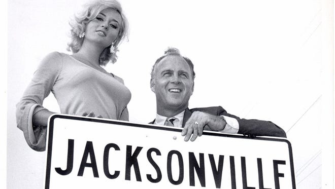 Actress Lee Meredith poses with Jacksonville Mayor Hans Tanzler in Oct 1968 at a new city limits sign erected after consolidation.