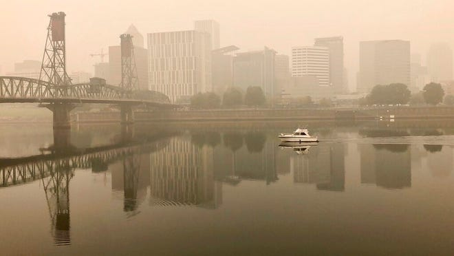 A view of downtown Portland from the East Bank Esplanade is seen on Monday. The entire Portland metropolitan region remains under a thick blanket of smog from wildfires that are burning around the state and residents are being advised to remain indoors due to hazardous air quality.