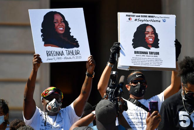 Signs are held up showing Breonna Taylor during a rally in her honor on the steps of the Kentucky State Capitol in Frankfort, Ky., June 25. The city of Louisville will pay several million dollars to the mother of Breonna Taylor and install police reforms as part of a settlement of a lawsuit from Taylor's family, The Associated Press has learned.