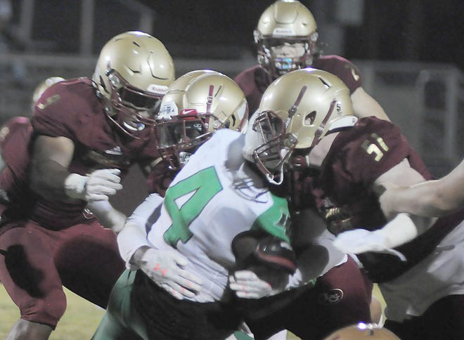 Lake Gibson's defense, including Eli Allen (51) and Roger Frazier Jr (9), stop Haines City running back DeShaun Muldrow for a loss during the first quarter Friday.