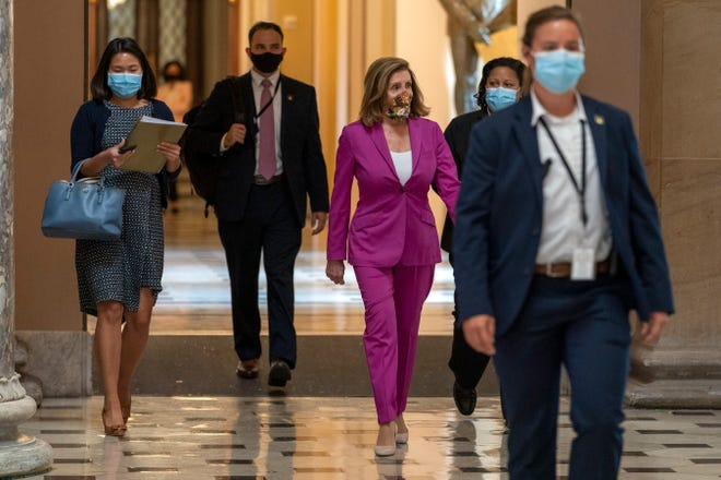 House Speaker Nancy Pelosi of Calif., center, walks to her office Monday on Capitol Hill in Washington.