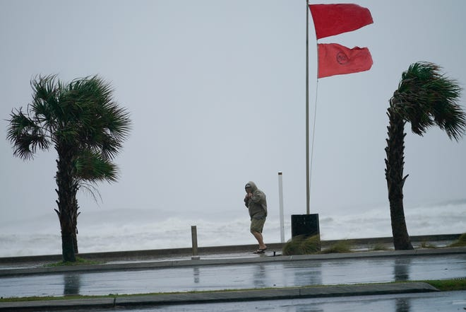 A man walks near the gulf as Hurricane Sally moves in Tuesday in Gulf Shores, Ala. Hurricane Sally, one of a record-tying five storms churning simultaneously in the Atlantic, closed in on the Gulf Coast on Monday with rapidly strengthening winds of at least 100 mph (161 kph) and the potential for up to 2 feet (0.6 meters) of rain that could bring severe flooding.