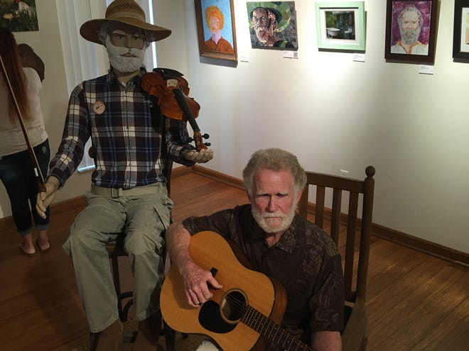 "Steve Morrison, known as ""Sticky Steve,"" plays an acoustic guitar inside the Lake Wales Arts Center during the opening day of an art exhibition devoted to him: ""Sticky Steve: A Home Brewed Life."""