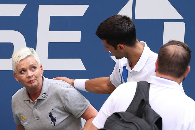 Novak Djokovic of Serbia tends to line judge Laura Clark, who was hit with the ball during his Men's Singles fourth round match against Pablo Carreno Busta of Spain on Day Seven of the 2020 U.S. Open on Sept. 6, in New York City. (Al Bello/Getty Images/TNS)