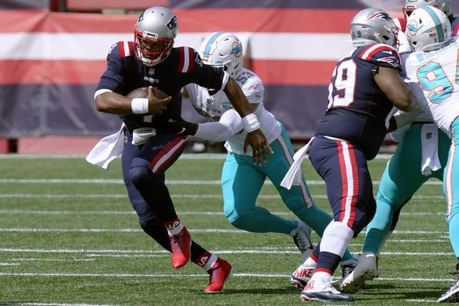 New England Patriots quarterback Cam Newton, front, runs from Miami Dolphins linebacker Kyle Van Noy (53). [STEVE SENNE/AP]