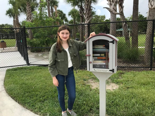 Grace Wodar stands next to the Little Free Library she donated to the Town of Jupiter. The library is located in Cinquez Park.