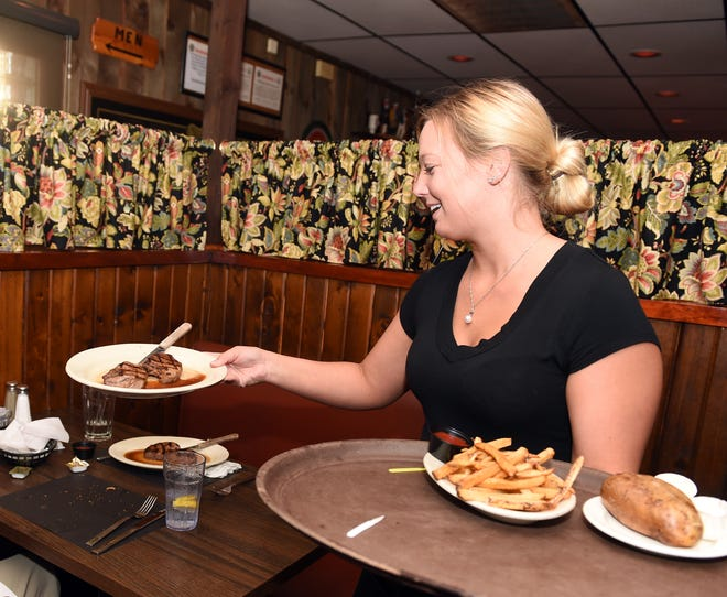 Ashley Lambert delivers steak dinners at Arnie's Steakhouse in Ravenna.