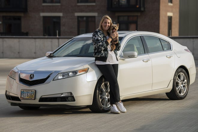 Portrait of Candace Dark of Columbus and her 14-year-old Yorkshire terrier, Apollo, alongside Dark's Acura TL at the Castle Garage in Columbus, Ohio, on Sept. 12, 2020. After rarely being driven from March through most of June, the battery and alternator in Dark's Acura were damaged from sitting unused for too long.  [Gaelen Morse/Dispatch]