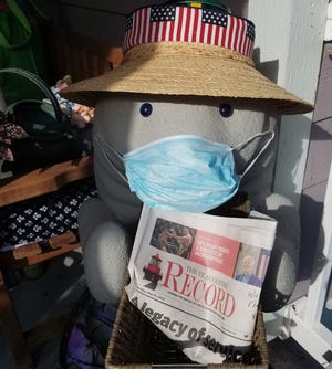 Manny the Manatee is masked up with The Record on a front porch in St. Augustine Beach.