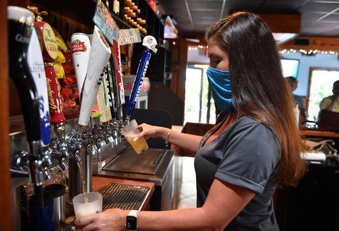 Bartender Lori Bailey pours beers for customers at West End Pub on Monday. Federal coronavirus relief applications will open on Wednesday in Sarasota County for small businesses.