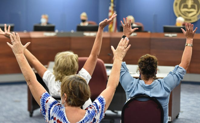 Attendees of Tuesday's meeting of the Sarasota County School Board raise their hands in support of a proposal that students no longer be required to wear masks while at school.