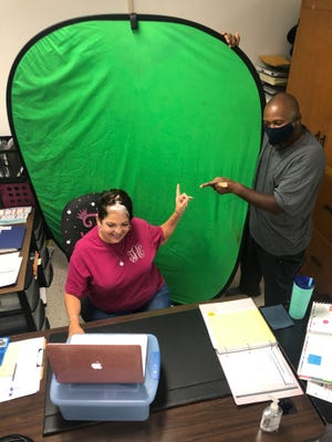 Teresa Alger and Anthony Keys, teaching virtually through the use of a green screen. [CONTRIBUTED PHOTO]