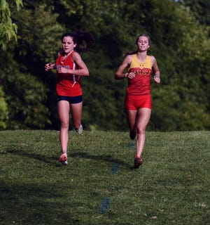 Ballard's Paityn Noe (left) runs with Carlisle's Ainsley Erzen down a hill near the two-mile marker of the Class A girls' race at the Mike Carr Invitational Monday at the Ballard Golf and Country Club in Huxley. Noe, ranked third, came in second to Erzen, ranked first, in a battle of two of the top runners in Class 3A. Noe's efforts helped the No. 1 Ballard girls win the Class A team title over No. 2 DC-G.