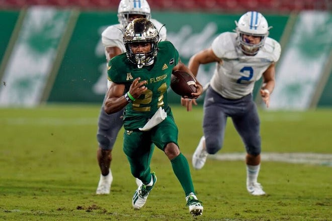 South Florida running back Brian Battie (21) outruns Citadel linebacker Andy Davis (2) during the second half Saturday. USF racked up 302 rushing yards in its 27-6 victory.