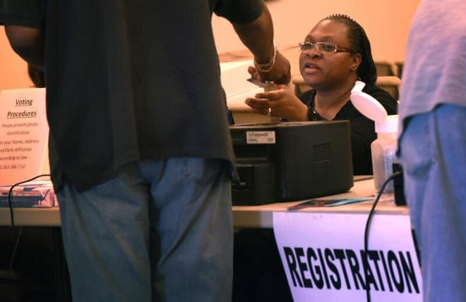 A poll worker checks a voter's ID during the March 15, 2016, primary in Fayetteville. North Carolina had a voter photo ID law in place for that election but it was later overturned in a lawsuit