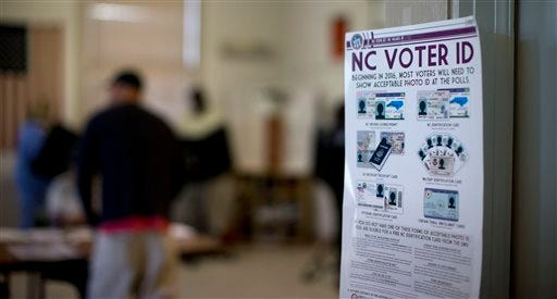NC Voter ID rules are posted at the door of the voting station at the Alamance Fire Station, Tuesday, March 15, 2016, in Greensboro, N.C. The state's new voter identification  law requires that voters show a photo identification before getting their ballot.  Voters in North Carolina, as well as Missouri, Illinois, Ohio and Florida are casting their ballots in primary elections Tuesday. (Andrew Krech/News & Record via AP) MANDATORY CREDIT