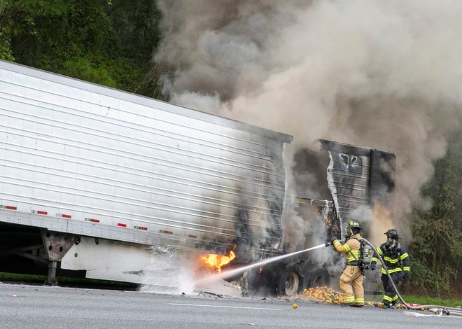 Marion County Fire Rescue firefighters work to douse the flames of a trailer full of oranges on I-75 south near Micanopy on Tuesday morning. The driver had disconnected the cab. The Florida Highway Patrol reduced traffic in north Marion County on I-75 to one lane in the area near the 372 mile marker while investigators sorted out the scene and accident debris was removed. Lt. Patrick Riordan said the truck's driver was able to unhook the trailer, so the only damage was to the trailer and its citrus cargo.