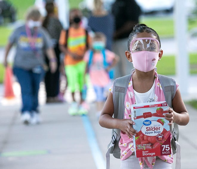 A first grader wears a face shield and mask combination while arriving for the first day of school.