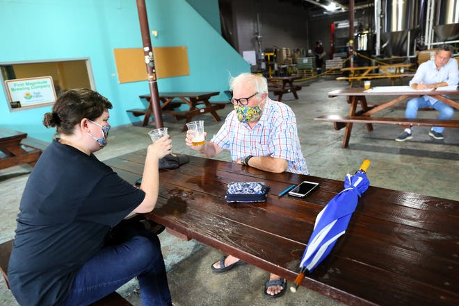Mike Moulton salutes the final sip of his beer with his daughter Linda at First Magnitude Brewing Company in Gainesville on Tuesday. The state on Monday began allowing bars and breweries to again serve alcohol for on-site consumption, after a similar attempt ended in June because of a lack of compliance with safety rules.