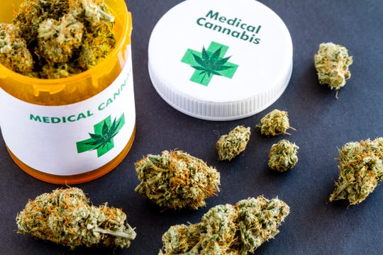 Medical marijuana buds in large prescription bottle with branded cap on black background.