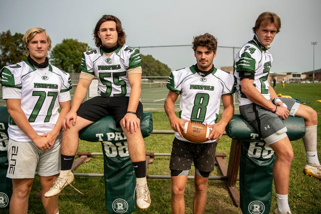 From left: Jack Boyd (77), Seth Clothier (55), Ryne Petersen (8) and Cody Hultink (24) pose for a picture on Monday, Sept. 14, 2020 at Pennfied High School in Battle Creek, Mich.