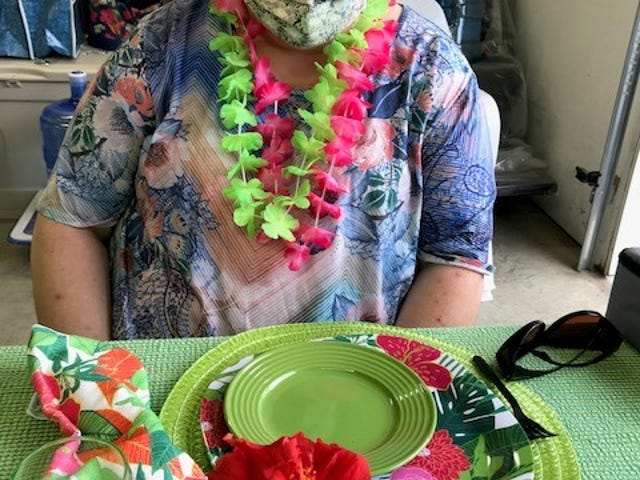Amy Vaughn sits ready for her luau dinner answering the place setting challenge set for Earth, Wind and  Flowers Garden Club members using  bold chartreuse and glowing red color.