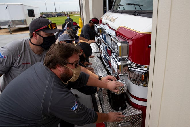 Emergency response workers at Gulf Coast Growth Ventures push two new fire trucks in to their station during a push-in ceremony on Tuesday, Sept. 15, 2020.
