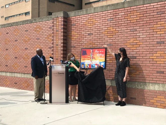 Camden County Freeholder Jonathan Youung looks on as mural artist Sonia Gonzalez and design contest winner Angela Brown unveil Brown's work.